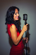 Attractive brunette woman singing into vintage microphone.