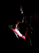 Silhouette of woman singing into vintage microphone.