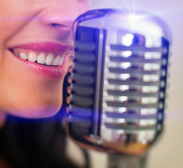 Close-up of female mouth singing into vintage microphone.