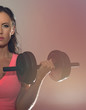 Attractive brunette woman working out with dumbbells.