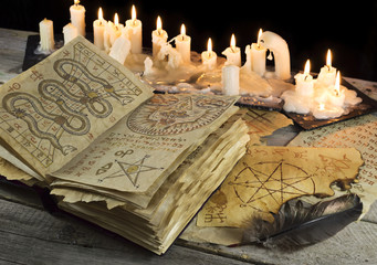 Grimoire book with candles and magic papers