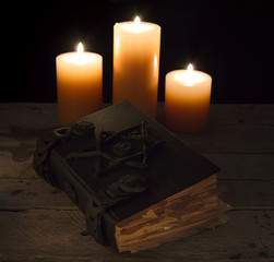 Black magic book with candles