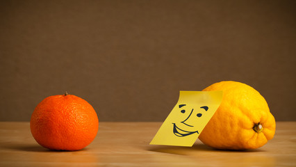 Lemon with post-it note smiling at orange
