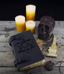 Magic still life with skull, book and candles