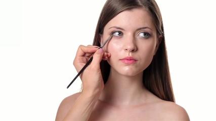 Beautiful woman applying make up on white background