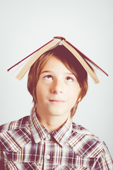 child with book over head