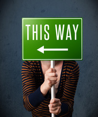 Young woman holding a direction sign