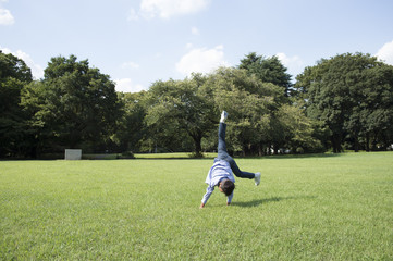 Boy to a cartwheel in grassland
