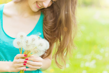 happy smiling girl with dandelions in the hands