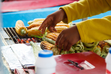 Person selling grilled corn outdoors in summer