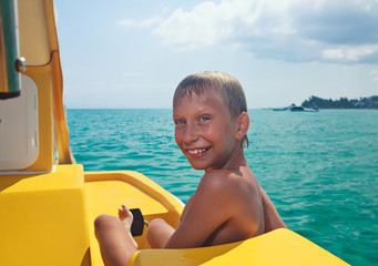 Funny child enjoying summer vacation on yellow catamaran