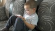 close up of little boy watching cartoon on touch pad