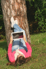 Young woman using tablet and lying in nature