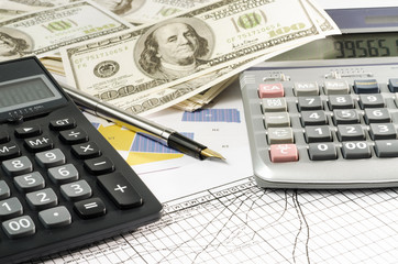 Fountain pen and calculator on the financial graph
