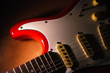 Red Old electric guitar against wood background