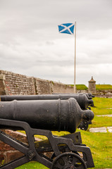 scottish flag next to cannons at fort george