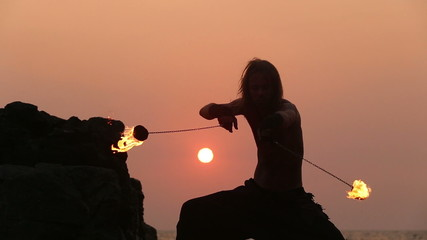 Male Artist of the spins fire poi on a rock