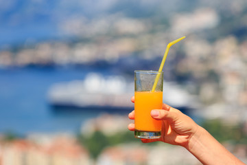 orange juice in hand against sea and mountains