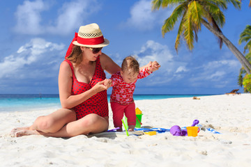 mother and little daughter playing on tropical beach