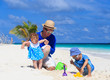 Father and kids making sand castle on the beach