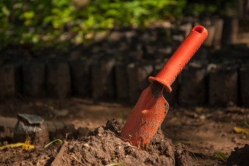 orange trowel  on soil