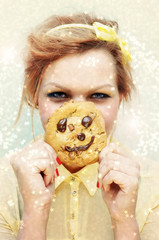 Happy woman hiding behind a smiling chocolate chip cookie.