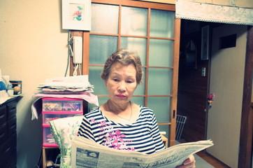 家の中で新聞を読む高齢者の女性
