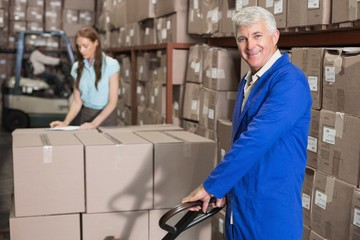 Warehouse foreman smiling at camera with trolley