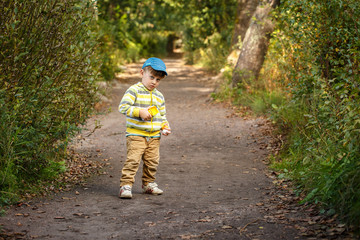 three year old boy playing in the woods
