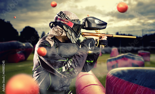 Paintball player in mid game being shot at - 69885245