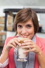 Pretty brunette enjoying her latte