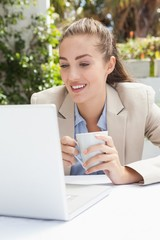 Beautiful businesswoman having a coffee using laptop