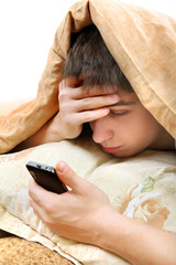 Teenager with Cellphone in the Bed