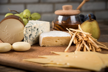 Various types of cheese, grapes, honey