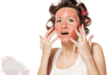 nervous young woman with curlers and a mask touching her face