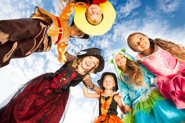 Many kids look down in circle wearing costumes