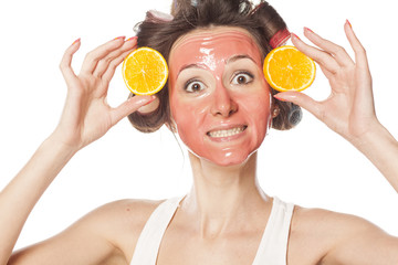 happy woman with a mask and curlers holding a pieces of orange