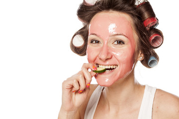 woman with a mask and curlers biting a piece of cucumber