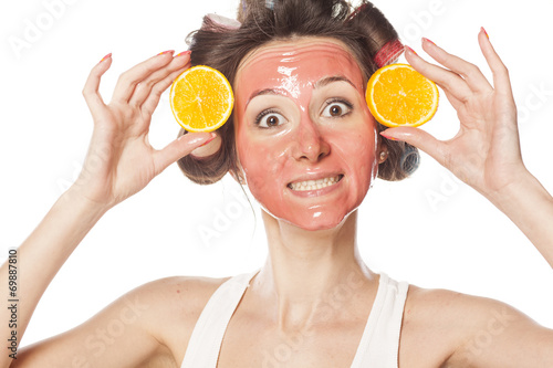 canvas print picture happy woman with a mask and curlers holding a pieces of orange