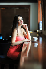 Pretty smiling woman sitting in the cafe with a cup of coffee