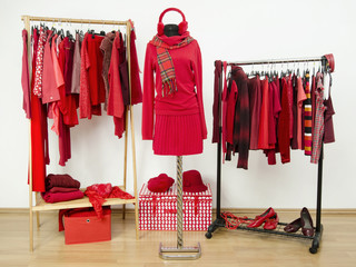 Wardrobe with red clothes on hangers and an outfit on mannequin.