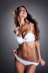 Seductive tanned model posing in white lingerie