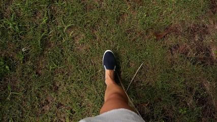 Female Legs in Street Slippers Walking on Green Grass. Slow