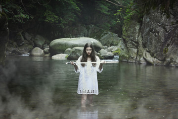 Dark girl with a sword in a mountain stream