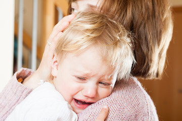 Mom holding  crying child