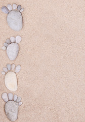 pair feet made of a stone on the sea sand