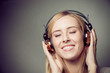 young blonde woman enjoying music on headphones