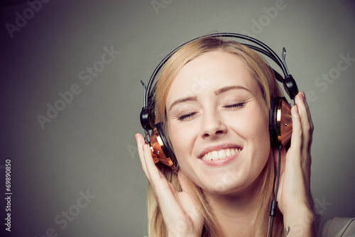 canvas print picture young blonde woman enjoying music on headphones