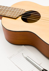 Little guitar and blank notebook with pen