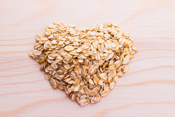 Heart-shaped oatmeal on wooden background